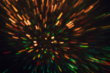 Abstract background of colorful lines in motion on black. Bokeh of defocused splashes, blurred yellow and green neon leds, fireworks and salute, space and sky backdrop