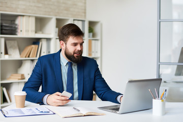 Portrait of young bearded businessman smiling while having video call meeting at desk in office