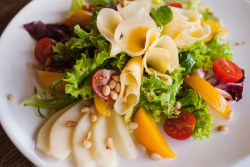 Lettuce salad with cheese and fruits on plate. Fresh vegetables decorated pine nuts, avocado, pearch and pear, serving in restaurant, close up picture