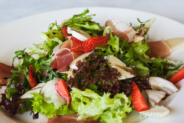 Salad lettuce with parma ham, blue cheese and strawberry serving in restaurant. Gourmet cuisine, close up picture