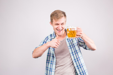 Happy young man holding and pointing on a beer mug