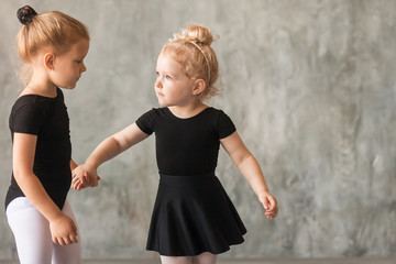 Two small fair-haired girls ballerinas in black packs, white pantyhose, white pointe shoes learn to dance a Russian ballet in a black dance studio