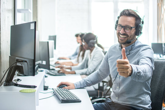 Cheerful male customer service operator showing thumbs up in office.