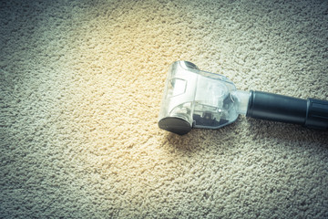 Close up, top view head of a modern vacuum cleaner being used while vacuuming a thick pile white carpet. Vacuuming rough carpet concept. Vintage tone.