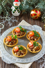 Tartlets with beans, meat and walnuts. Beautiful Christmas and New Year's food background. Selective focus.