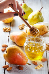 Tasty pears with honey and nuts on wooden table
