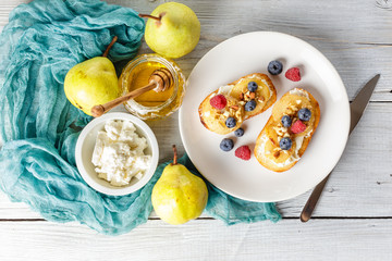 Crostini with ricotta cheese, fried pear, nuts and honey, decorated with raspberries and blueberries