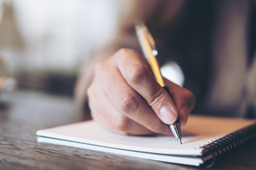 Closeup image of business woman writing on blank notebook on wooden table background