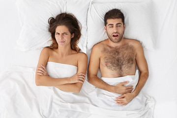 Young brunette female feels annoyed with husband who sleeps very loudly, interrupting to dream. Man looking nightmare during night. Pretty female has insomnia after hard work. Late time concept
