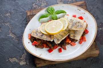 Slices of fried sudak fish with vegetable saute and lemon, brown stone background, studio shot
