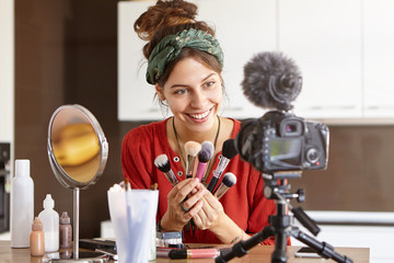 Successful video blogger celebrity making another video content for blog in social networks, testing powder brushes at home, sitting at dressing table with cosmetics, looking at camera fixed on tripod