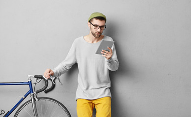 Handsome unshaven guy in eyewear, holding digital tablet, going to repair bicycle, watching video, consulting how to do it. Repairman using internet for watching bicycle races online, isolated on grey