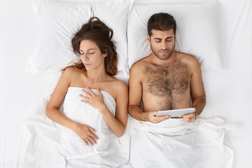 Top view of serious bearded businessman lying in bed awake busy working online using digital tablet while his wife sleeping next to him. People, family, relationships and modern technology concept