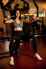 Active sporty woman workout arms in fitness club gym