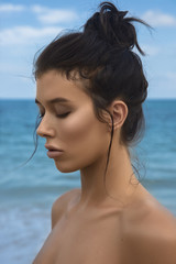 Close-up portrait of a young beautiful well-groomed girl in profile on a blue sky and sea background. Bright lighting - sunlight. Bright colors. Smooth, shiny, well-groomed skin, tan. Advertising.