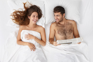People, love, relationships, leisure, bedtime and happiness concept. Top view of happy young married couple lying in bed with white linen: unshaven man reading newspaper and talking to his wife
