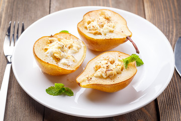 Pears baked with Ricotta cheese, nuts, honey and cinnamon on rustic wooden background