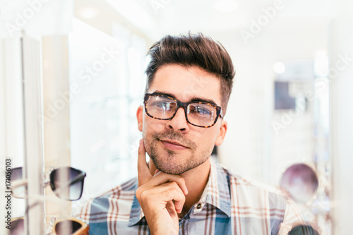 a07828b8b5 Handsome young man choosing eyeglasses frame in optical store ...