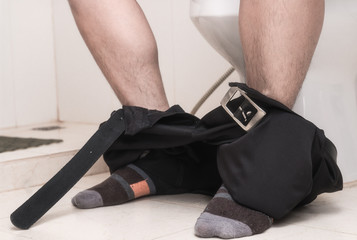 Young man using toilet and removing his trousers down on the floor.