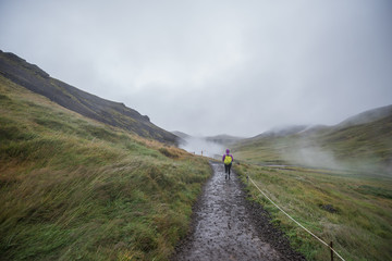 Walking along the geothermal river at Reykjadalur Valley near  Hveragerdi, Iceland