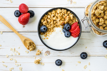 bowl of granola with yogurt, fresh berries, strawberry on wood table.