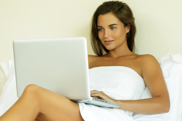 Woman lying on the bed and using laptop pc