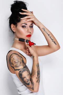 Young woman tattooist with a tattoo-machine in her hand