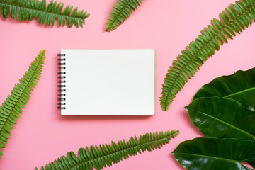 Flat lay design of blank notebook and leafs on the pink pastel background. with copy space