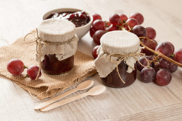 Homemade jam in small glass jars. Fresh grapes in background.