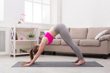 Woman training yoga in dog pose.