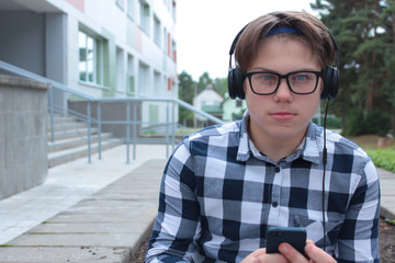 Boy teenager (schoolboy or student) in a shirt, smiles in glasses, listens to music on the phone, red backpack, school background.