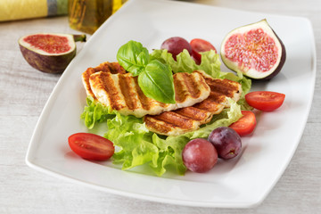 Grilled slices of halloumi cheese served on the plate with fig, grapes, lettuce, tomatoes and basil leaf. Halloumi is popular in Cyprus, Greece, and Turkey.