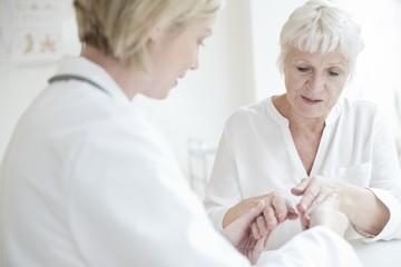 Female doctor examining senior patient's hand