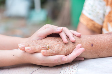 Old and young holding hands, Care for the elderly concept