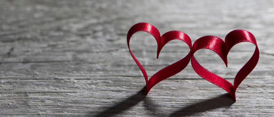 Two ribbon hearts on wood