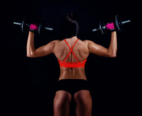 Portrait of an attractive young fitness woman in sportswear doing workout with dumbbells on black background. Tanned sexy athletic girl. A great sporty female body. Back view.