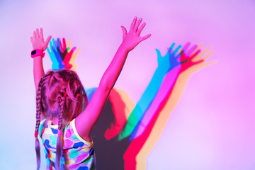 Girl stands at the wall with her hands up, on which her silhouette is reflected in different colors. Back view