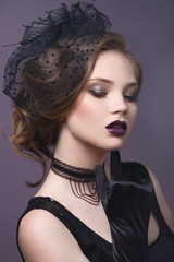 Beauty portrait of a beautiful girl in a gothic image on a purple background.