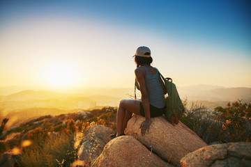Rear view of woman hiker sitting on rock on top of hill while looking at sunset over San Diego California Wall mural