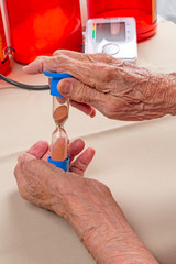 Hourglass in the hands of an old woman