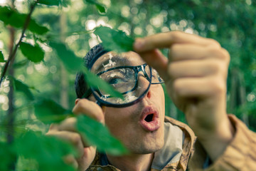 Photo of young ecologist with magnifying glass