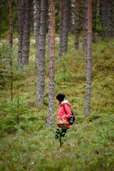 young woman in red jacket enjoying nature in forest. Latvia