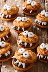 Halloween food: monsters of nutty cookies with chocolate cream close-up. vertical
