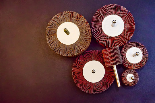 Flap Wheel. A pile of color abrasive Flap Wheel industrial on wood background texture. sandpaper wheel tool - professional equipment