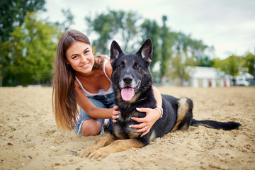 Portrait of a girl with a dog by a German shepherd in the summer.