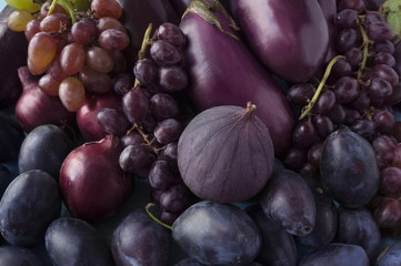 Blue and purple food. Background of fruits and vegetables.  Fresh figs, plums, onions, eggplant and grapes. Top view.