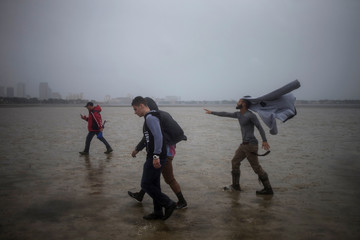 The Tampa skyline is seen in the background as local residents are hit with gusts of wind while walking into Hillsborough Bay ahead of Hurricane Irma in Tampa