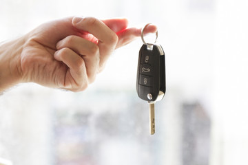 Hand with a car key. salesman with car sales