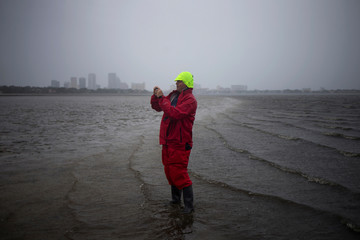 The Tampa skyline is seen in the background as a man takes photographs after walking into Hillsborough Bay ahead of Hurricane Irma in Tampa