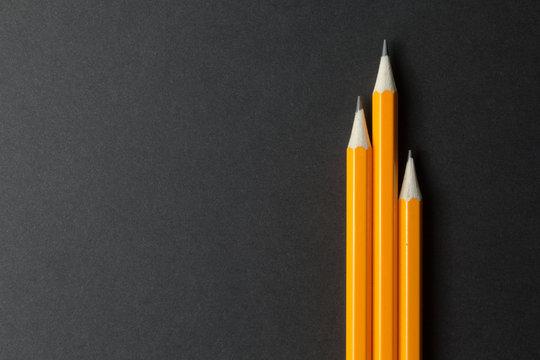 Three yellow pencils on black paper, empty space.